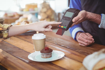 Customer entering pin number into machine at counter in cafe